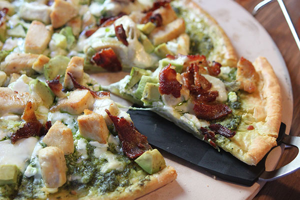 Gluten-free pizza with chicken, bacon, avocado, pesto, mozzarella, and goat cheese.